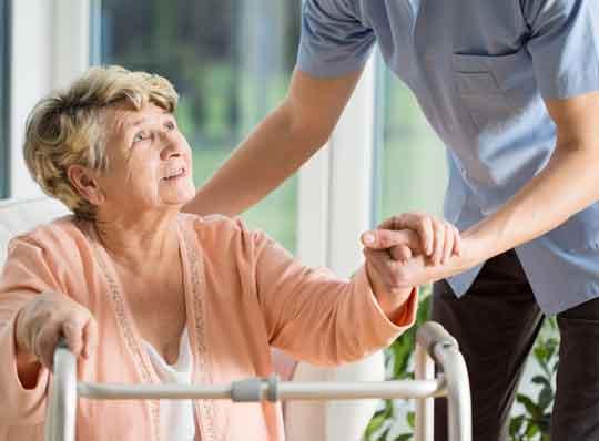 Elderly woman being helped by a nurse